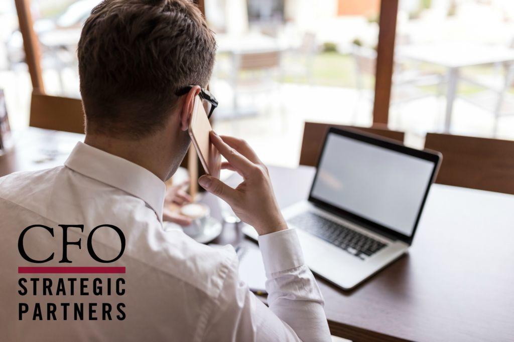 businessman using smartphone and laptopÿ
